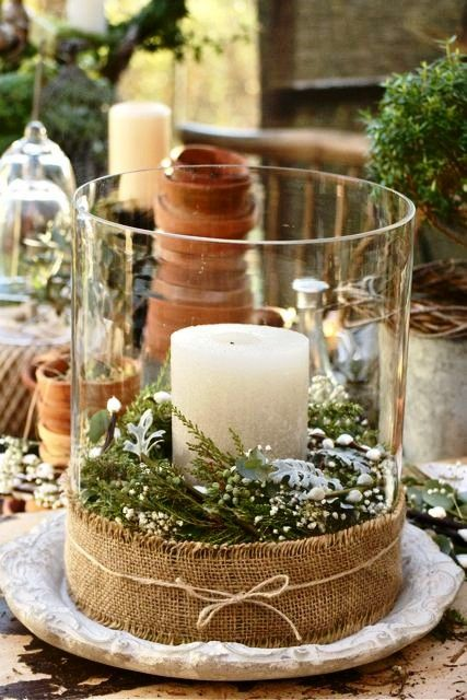 Glass hurricane jar, glue burlap to the bottom, place candle of your choice in middle of glass jar, fill with flowers and clipping of your choice. Very easy and nice decor piece. You can even change it for the seasons. Kat wedding vases???