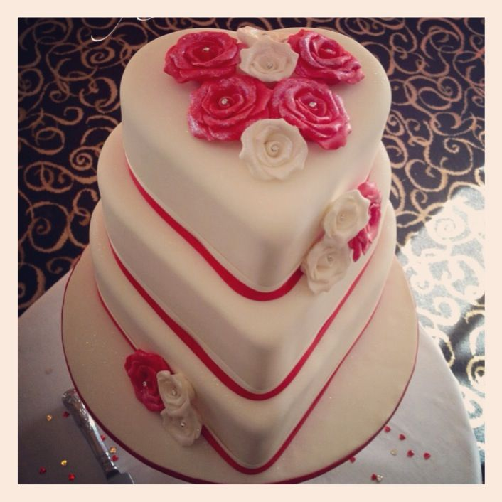 3 tier heart shaped wedding cake with ivory and red handmade roses.