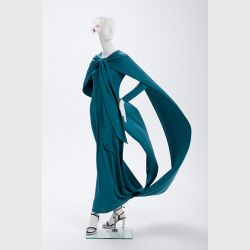 This Dress was designed by Gorgio di Sant'Angelo in 1974. It is a teal synthetic jersey dress. Source: Phoenix Art Museum
