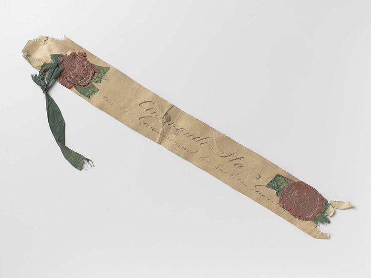 Anonymous | Commander's baton of the Dutch Governor of the Gold Coast, Anonymous, c. 1850 - c. 1900 | Langwerpig papier met aan beide uiteinden rood lakzegel van het gouvernement ter kuste van Guinee met groen lint. Midden opschrift: Commandostaf van het Gouvernement ter kuste van Guinee.