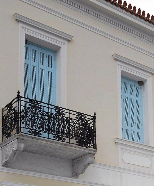 A swallow nest in the window of Neoclassical house, one of the many of Spetses…