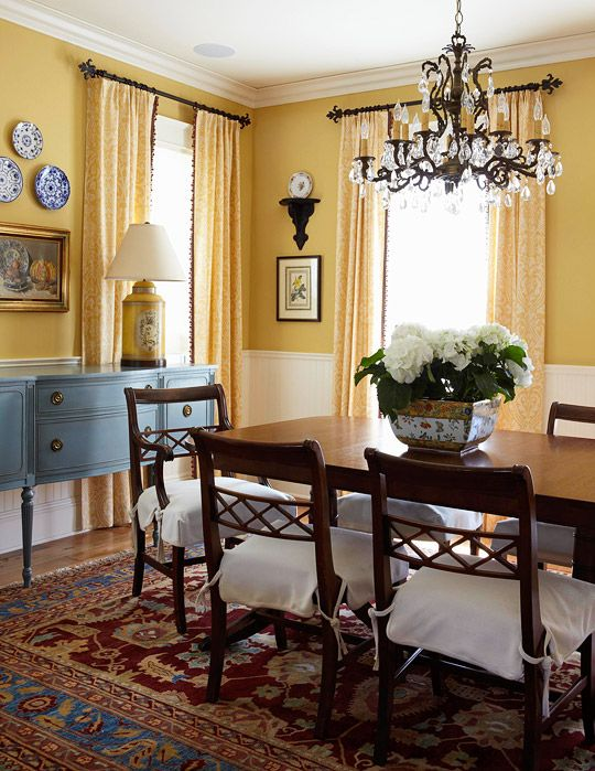 The formality of a mahogany dining table is toned down by a turquoise sideboard and sunny yellow walls. - Traditional Home ® / Photo: Luca Trovato / Design: Kathy Bush