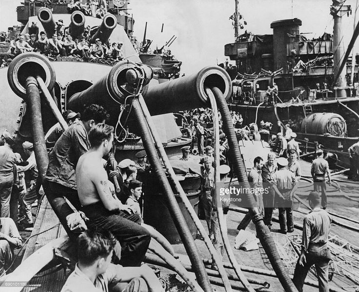 Sailors attend water pumps that have been placed down the barrels from one of the bow 14 in (360 mm)/45 cal guns (4×3) gun turrets of the USS Pennsylvania (BB-38) a Pennsylvania class super-dreadnought of the United States Navy whilst undergoing repairs following a Japanese torpedo strike whilst at anchor in Buckner Bay on 12 August 1945 at Buckner Bay in Okinawa, Japan.