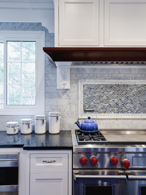 A Wall Of Marble Subway Tile Forms Into A Framed Blue And Brown Mosaic Tile  Backsplash That Adds Visual Interest To This Transitional Kitchen.