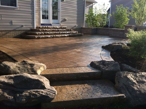 Brown Travertine Stamped Concrete Patio with Rock Inlays