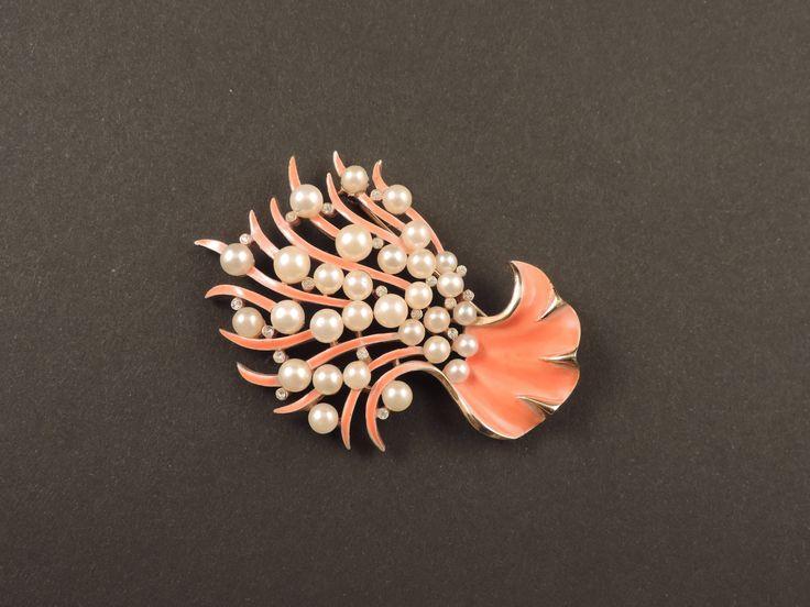 Spilla americana degli anni '60 a forma di ramo di corallo, in metallo dorato rodiato e decorata da smalto color corallo, perle d'imitazione e piccoli strass bianchi, imitanti i diamanti. Firmata Trifari, è completa di chiusura di sicurezza. In vendita su www.mirabilia.gallery per 147,00 € (Iva inclusa).