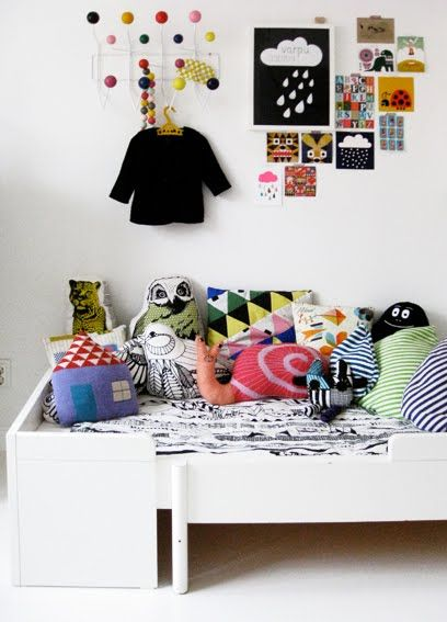 I know it's a kids room but I love the colours and the random cushions...and the placement of the pics and the eames wall hooks (i think). I love it all.