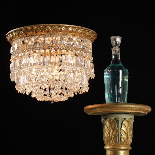 Lampada a soffitto dalla forma circolare, presenta cornice in legno intagliato e dorato e pendenti in cristallo.
