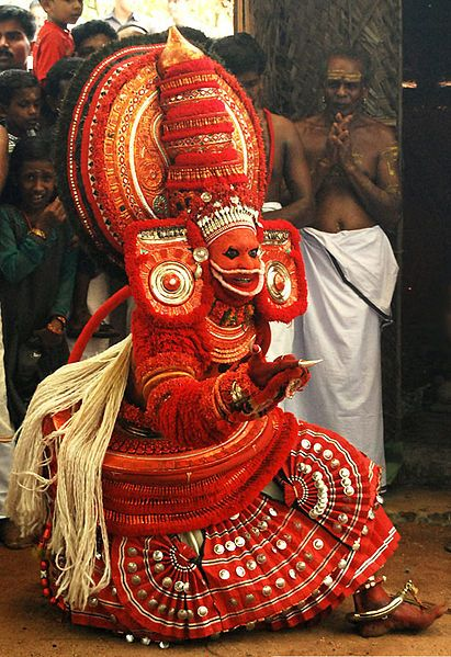 Theyyam, Hindu ritual worship of Kerala, India. A folk religion, several thousands of years old. Theyyam is a god & they are seeking it's blessing. This dance is an invocation performed in front of the shrine, or in houses as ancestor worship.