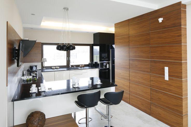 Element drewniane wprowadzano do kuchni jako zdobniki dekoracyjne. Zdobią one ściany nad blatem, a następnie przechodzą w wysoką zabudowę. Projekt Piotr Stanisz. Fot. Bartosz Jarosz.