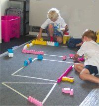 Use blocks and masking tape to makes shapes on the floor! Fun shape activity for preschoolers or toddlers.