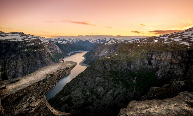 A man practicing head stand on trolltunga. The sun was going down and light was beautiful. I enjoyed the view among few other that stayed that night at this amazing location.