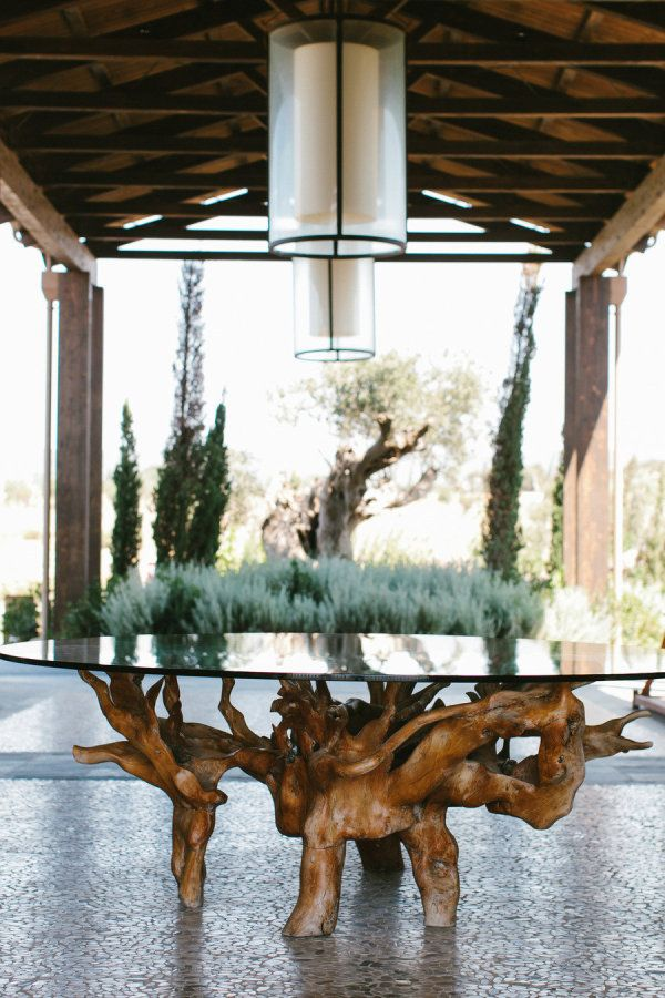 Outdoor table made from the roots of big vine or tree. PS Love the pendants!