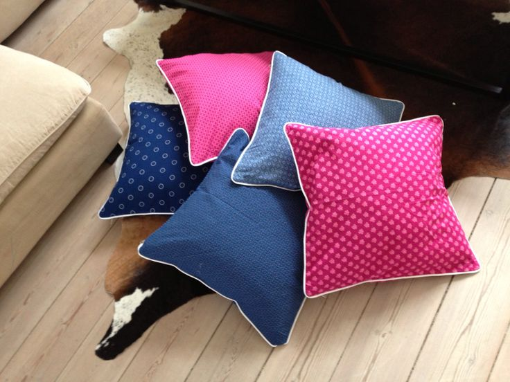 My self made cushions from traditional Zulu ShweShwe fabrics in pink and blue with white piping, by Da Gama Textiles, Durban