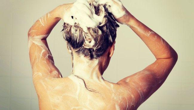 Frau shampooniert sich die Haare