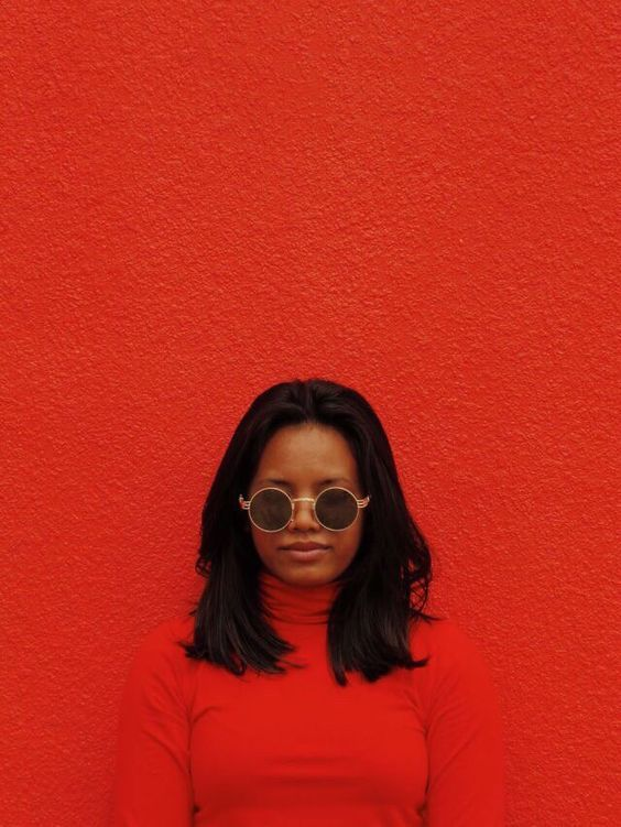 Round glasses on red background portrait shot