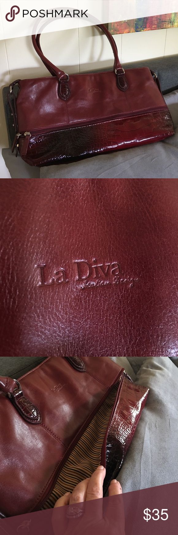 La Dive Italian design large purse/totebag/satchel La Diva Italian design large combination faux leather and vinyl.  Is gorgeous.  Worn once.  Has a built-in wallet and two very roomy pockets inside incuding a zipper pocket and a phone pocket.  Along the front of the purse toward the bottom is a zipper pocket the full length of the purse really nice.  Would really be perfect for a trip or any occasion.  Color is a reddish brown.  The dark spot on the bottom of the purse is part of the…