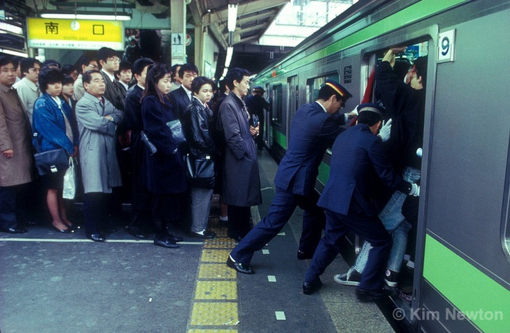 Japanese commuters wait in line for the next train, while people pushers push passengers onto the Yamanote line subway during the morning rush hour at Shinjuku station in Tokyo, Japan. The daily ritual is performed to maximize the number of commuters on trains.