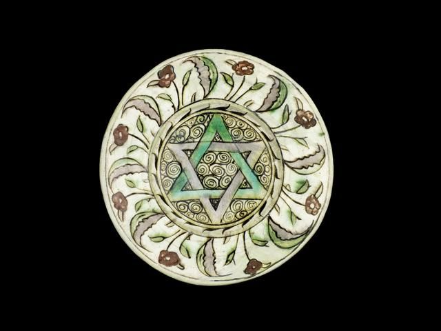 An Iznik pottery plate, Turkey, Circa 1600, with wide sloping rim, decorated in polychrome with a six pointed star on a ground of scrolling motifs, the rim with a band of floral sprays interspersed by large foliate motifs 25.2 cm. diam.
