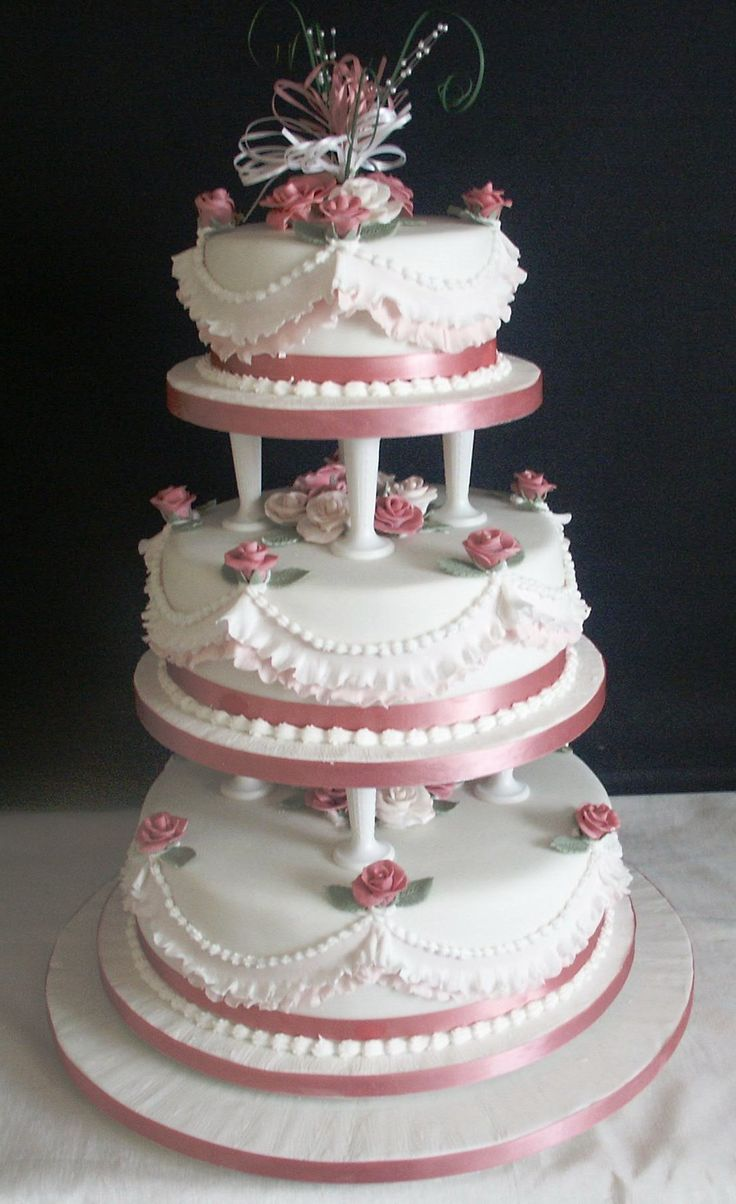Traditional Wedding Cake Supported On Pillars With Fondant Sugar Flowers And Frilled Side Design Can