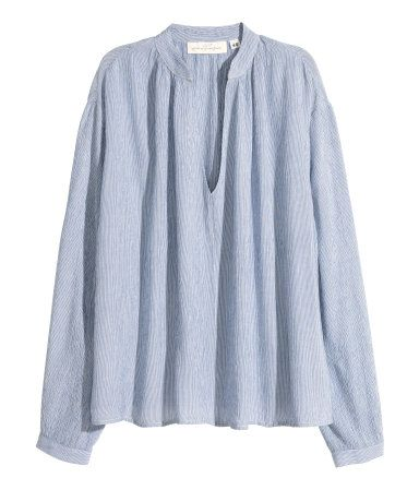 Wide-cut blouse in gently crinkled woven fabric with a V-neck and long sleeves with buttons at cuffs. Light blue. | H&M Pastels