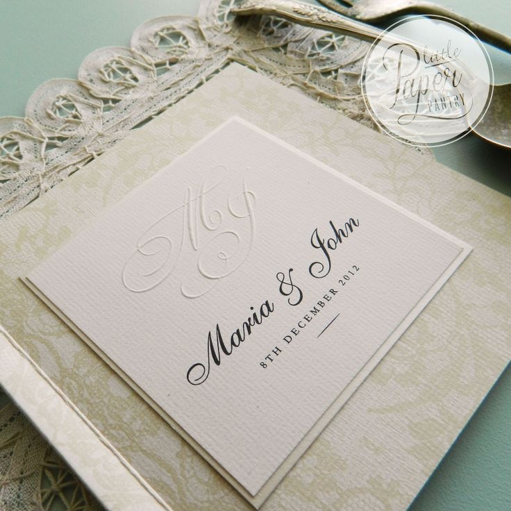 Embossed initials on a layered booklet invite with lace pattern.