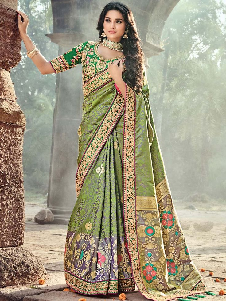 Conspicuous olive green and grey two tone banarasi silk saree with work, border and tussles is adding a spark to outfit. Every woman would want to drape this ensemble to get more beautiful looks.