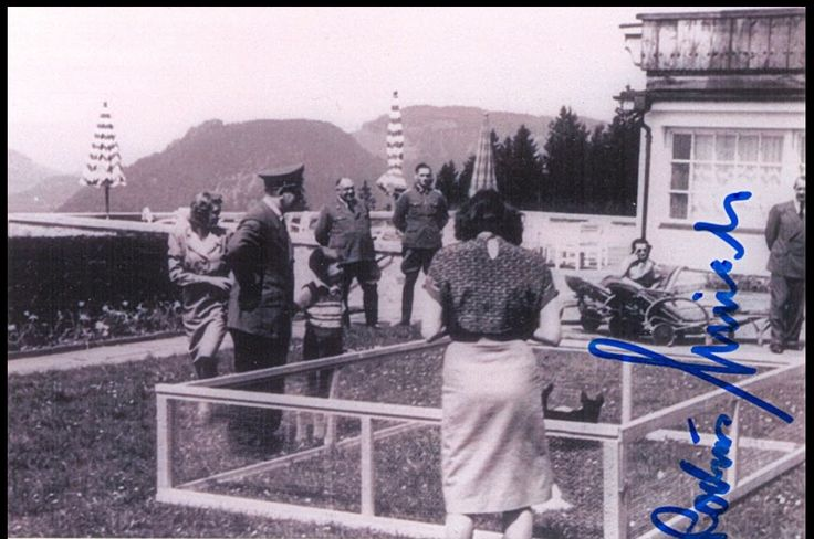 Adolf Hitler watching puppies with a young child. We can see Eva Braun, Dr. Theodor Morell and Rochus Misch here, and the signature belong to Herr Misch