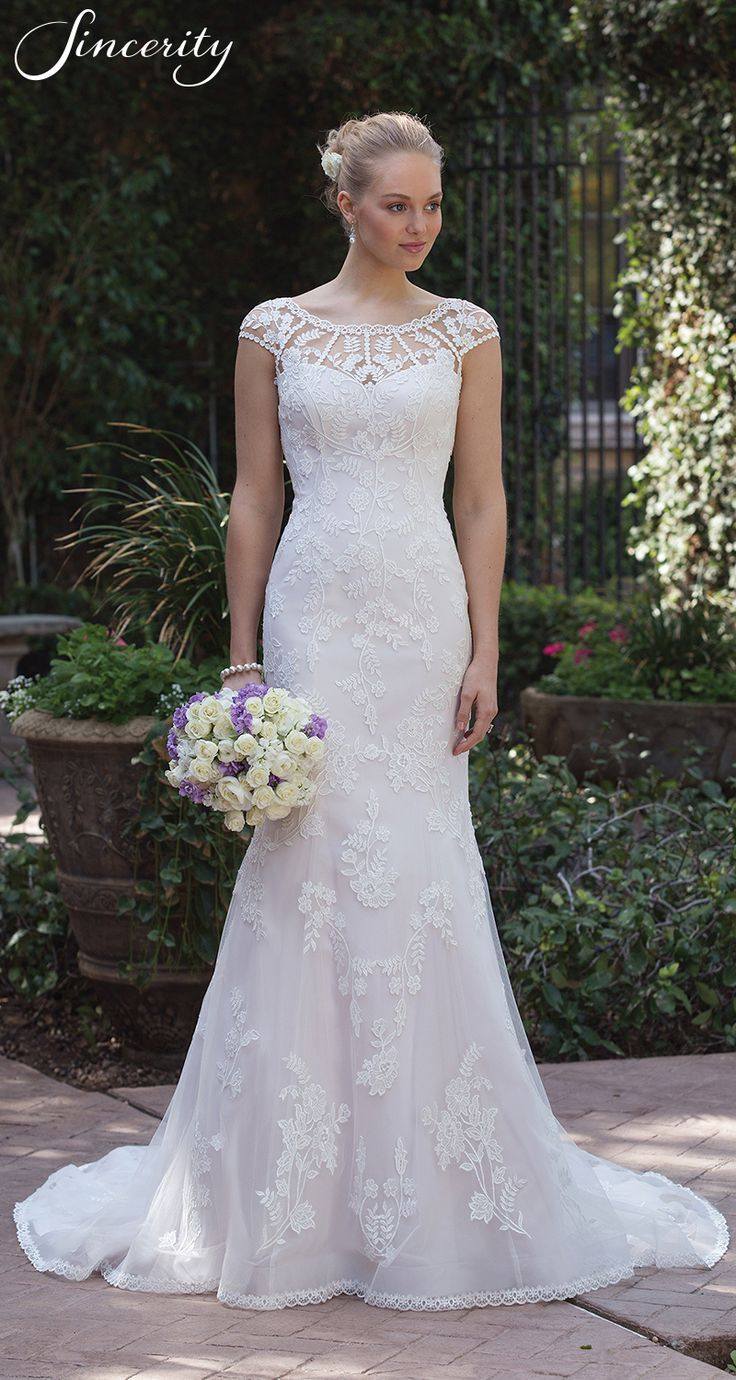 Style 4018: Venice lace and appliqués adorn this wedding dress with its illusion Sabrina neckline and illusion back. The fit and flare skirt is accented by floating Venice lace and a finished scalloped trim lace. Buttons start at the top of the back and cascade to the bottom of the hem.