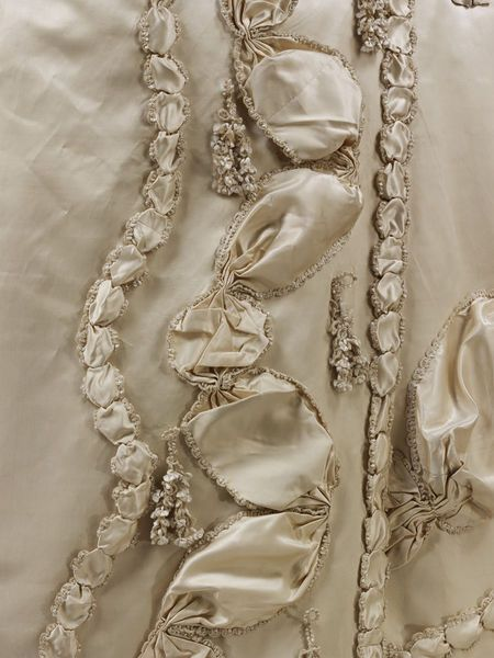 Detail decoration, court dress à la Francaise (sack back gown), Greiat Britain, 1775-1780. White silk satin, broad and narrow strips of the white silk satin have been edged with silk fringe, gathered and applied to the gown in undulating lines. The fringe is made of looped and knotted floss silk and chenille thread.