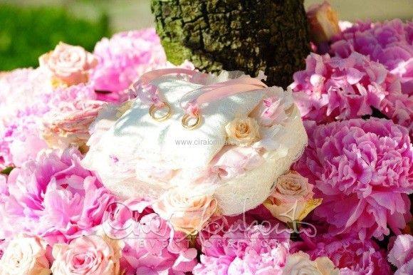 Fiorisce la primavera nel portafedi romantico in merletto e raso rosa di un matrimonio in costiera