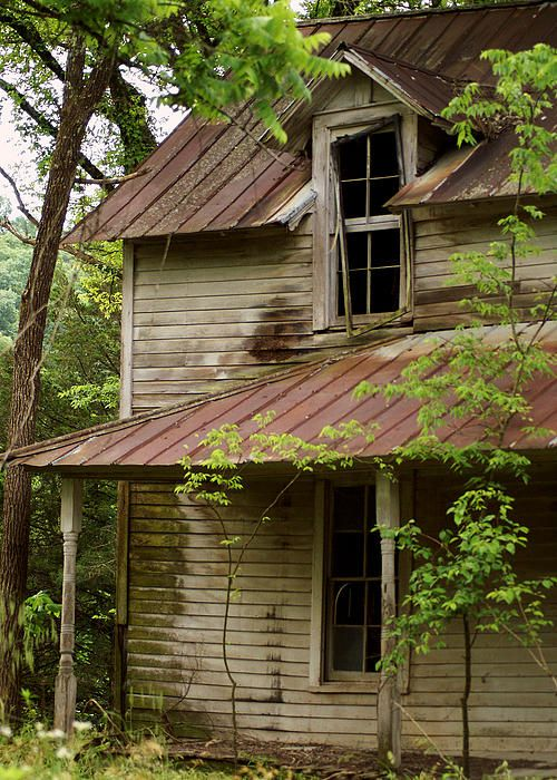 The windows and rusted tin roof of this old abandoned house tell a story from…