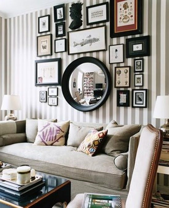 Love how the large round mirror plays off the striped wallpaper and straight lines of the frames. The silhouette on top also provides the eye a bit of relief and it being in black versis another color makes it blend nicely with the whole scheme. Notice the tight spacing of everything. The closer spacing creates a larger composition where all the parts are in relation to each other and therefore they become a whole.