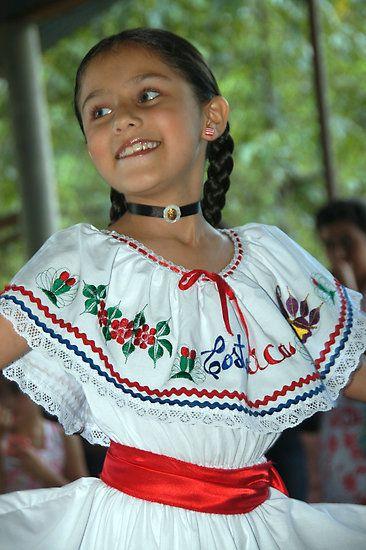 Esta chica está vestida con un vestido tradicional de Costa Rica. Ella está haciendo un baile folclórico.