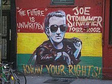 "A photograph of the painting of the memorial mural of Joe Strummer on the wall of the Niagara Bar in the East Village in New York City. The mural depicts Joe (center) surrounded by the words ""THE FUTURE IS UNWRITTEN"" (on the left), ""JOE STRUMMER 1952–2002"" (on the right), and ""KNOW YOUR RIGHTS!"" (bottom) on a horizontal tricolour of red, yellow, and green background"