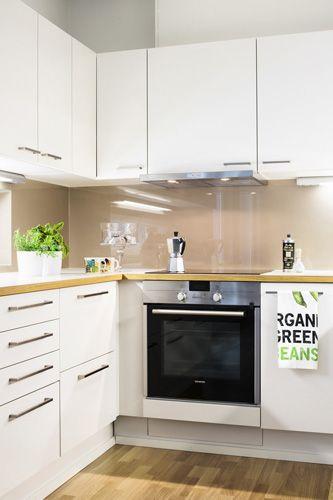 Valkoinen keittiö pehmeällä ruskealla taitettuna Tapiolan Kellosepässä Photo: Skanska Kodit http://kodit.skanska.fi/