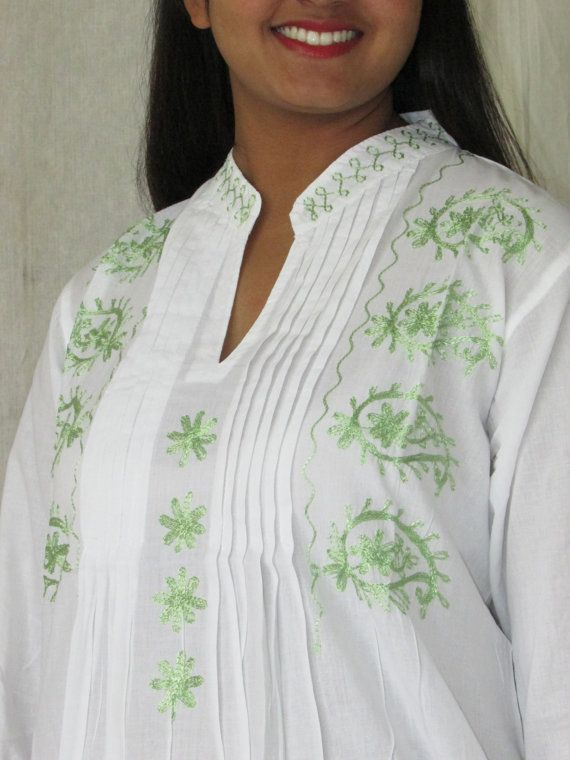 This white collared 100% cotton tunic/ Indian kurta is very soft and light to wear. Comes with the long sleeves with green embroidery around