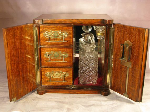 Antique 19th Century Victorian Period Tiger Oak & Brass Mount Cigar Smokers & Decanter Cabinet Circa 1890 A wonderful desk top cigar smokers and decanter cabinet constructed in the manner of a safe in beautifully grained Tiger Oak with ebony string highlights.  Brass mounts and handles, the shield cartouche lock cover slides open to reveal a fully operational lock with original key. The twin doors open to reveal a fully fitted interior again with brass mounts consisting of three draws...