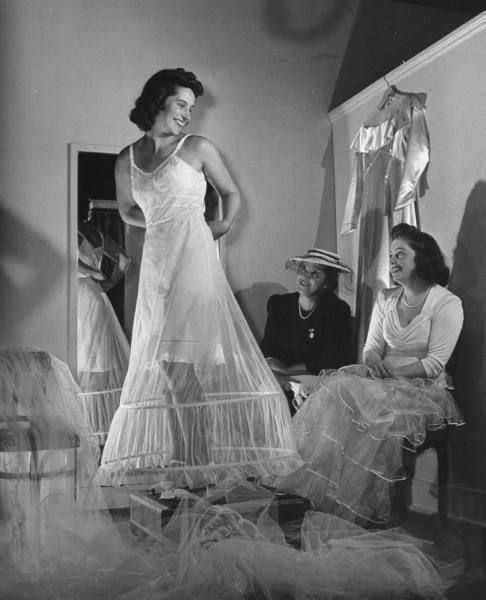 A 1940s bride getting ready to put her wedding gown on, complete with a modest sized hopped crinoline underneath.