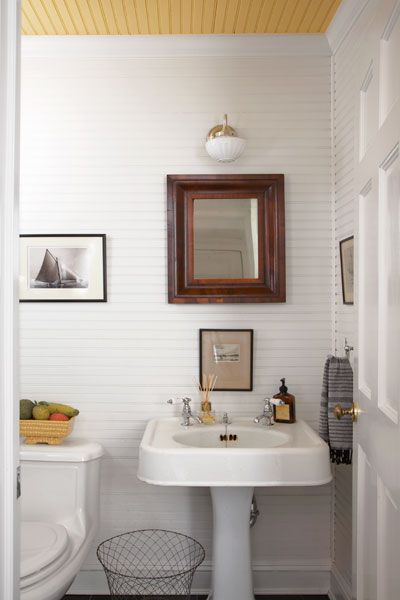 Painted paneling on the walls and ceiling, a vintage-style sconce, and a salvaged pedestal sink with separate taps give the refurbished hall bath an updated period look.
