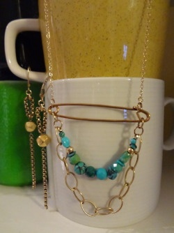 A unique necklace of various shapes, colors and sizes of turquoise draped with goldfill chain suspended by a vintage safety pin.  East Indian faceted gold foil beads with vintage chain earrings.