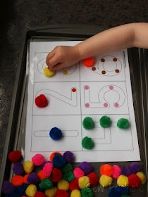 Magnets stuck to pom-poms, baking tray & number outlines to learn counting!