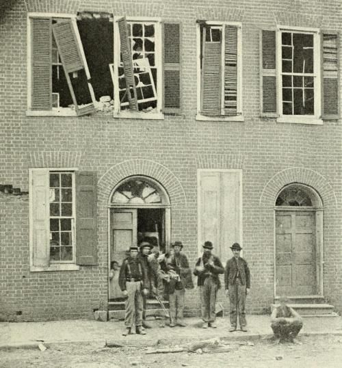 """chubachus:  """" Portrait of a group of Union soldiers and civilians posing in front of the artillery shell-riddled Dunlop House on Bollingbrook Street in Petersburg, Virginia, shortly after the end of the Siege of Petersburg, April 1865.  """""""