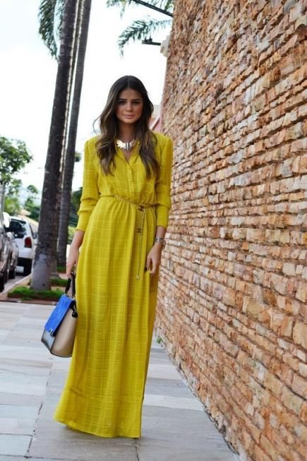 Long-sleeve maxi dresses are a fashionable and effortless style to bundle up in for a fall wedding. We love how Thássia of Blog da Thassia dressed up this solid gold with a bold choker and bright bag for contrast.
