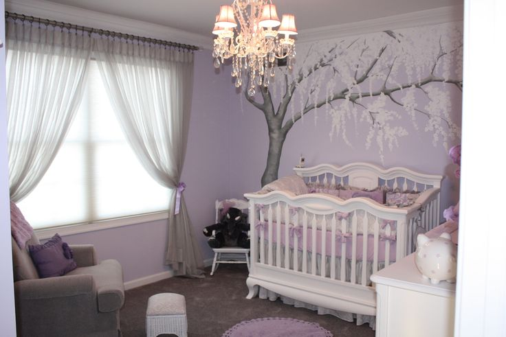 "This beautiful nursery was designed by the mommy-to-be, who has since become a mommy. The fabrics are lavender, silver and white. The bedding is lilac-gray-silver damask bedding by Carousel Designs. I painted a soft metallic silvery Cherry Blossom tree that shimmers and is embellished with crystals. The quote above the changing table says ""From the moment I first saw you I have been waiting for you.You know I will adore you....til eternity...""~Be My Baby lyrics"