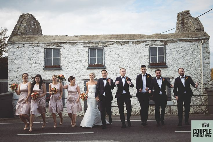 The bridal party in front of a cute white washed ruin near the church. Weddings at Durrow Castle photographed by Couple Photography.