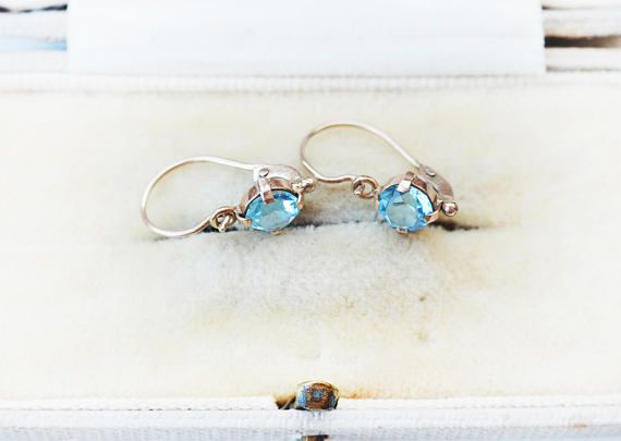 This is a cute 10k antique topaz earring. Antique style front closure.Antique market find. Would be a great gift for someone who has blue eyes, as this colour matches really well and enhances blue eyes. Cute, simple, classica. These types of earrings with front closure and delicate dainty