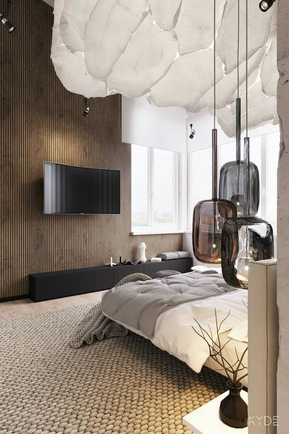 Intesting bedroom decor, rope style carpet, floating bed, curved tv screen similiar to the Samsung 4K UHD TVs and unique lighting fixure above the side table.