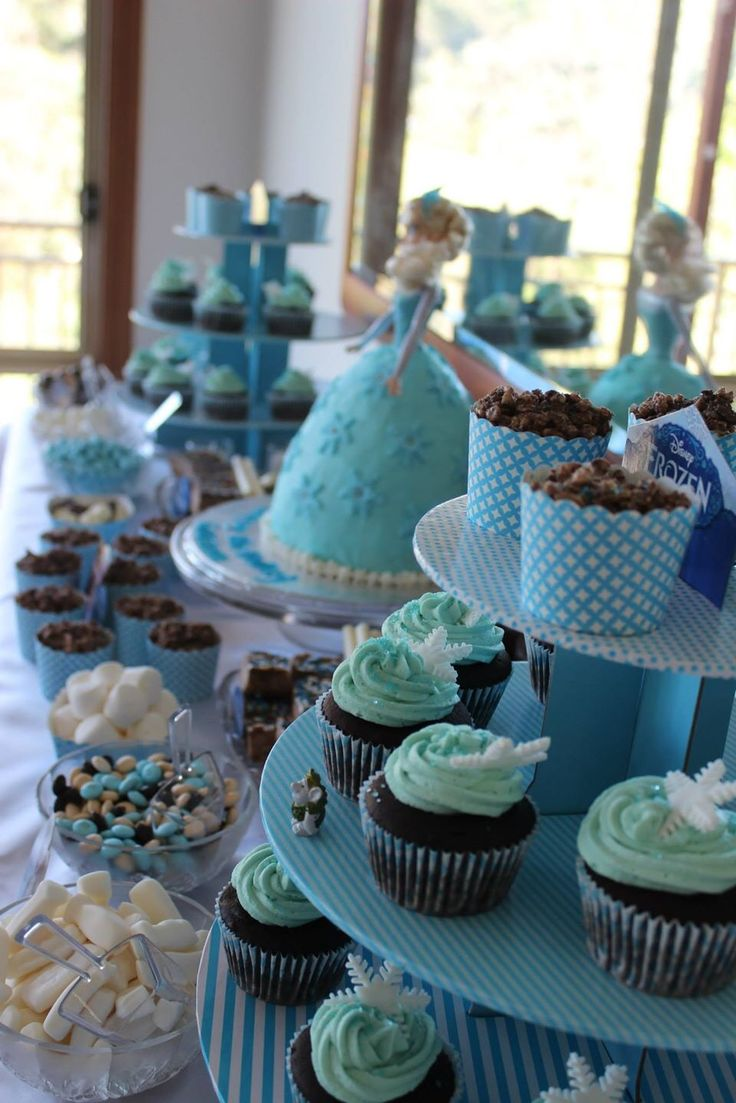 Frozen birthday party blue lolly buffet. Elsa doll cake, snowflake cupcakes