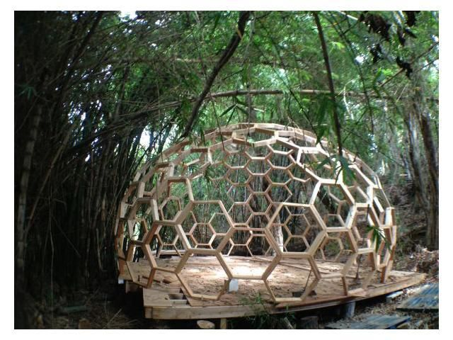an open structure made of shapes for over the fire area with board-lego benches